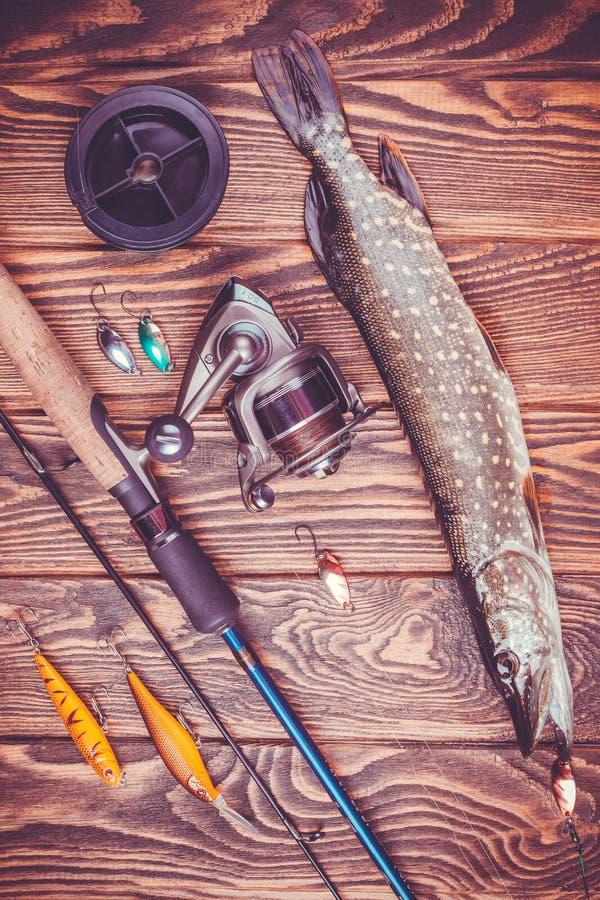 Рыболовные снасти и щука на деревянном столе стоковая фотография
