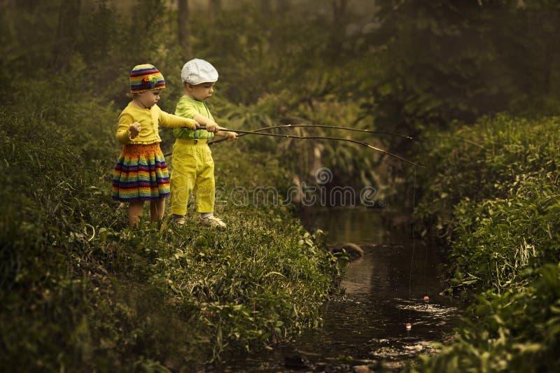 Рыболовство маленькой девочки и мальчика стоковое фото