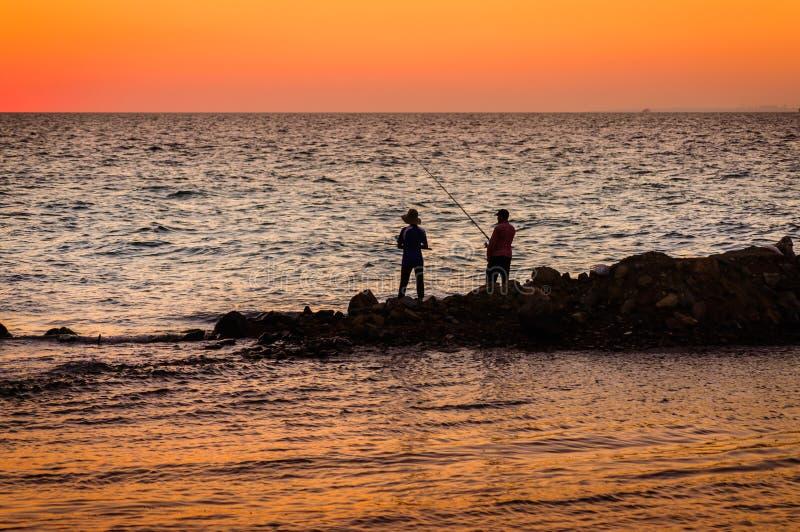 Рыболовы в мягком заходе солнца стоковая фотография rf