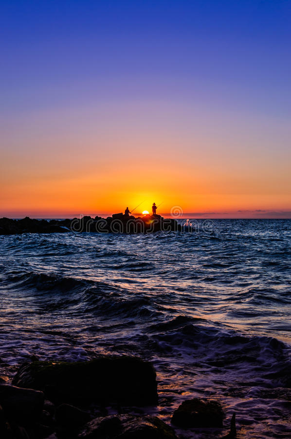 Рыболовы в мягком заходе солнца стоковое фото rf