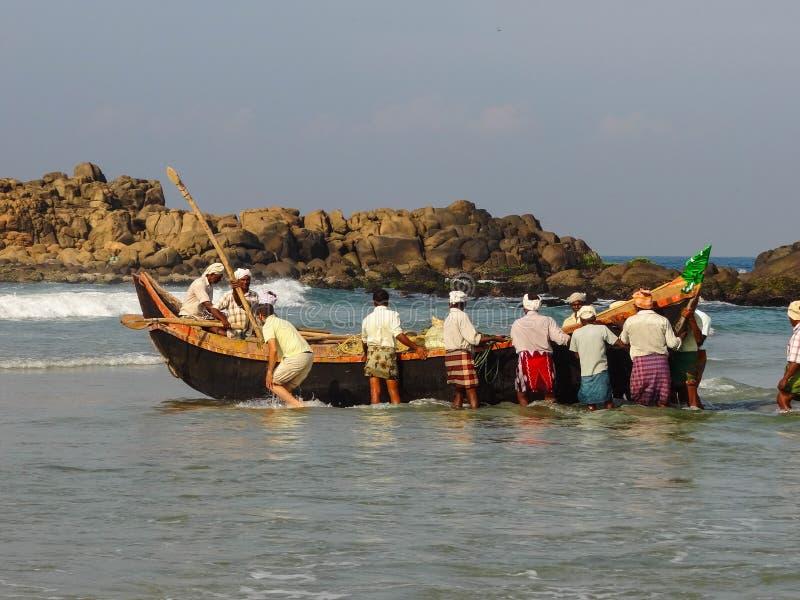 Рыболовы гребя шлюпку стоковая фотография rf
