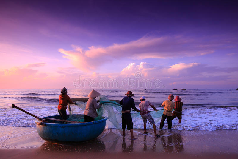 Рыболовы которые волочат сети на восходе солнца стоковые изображения