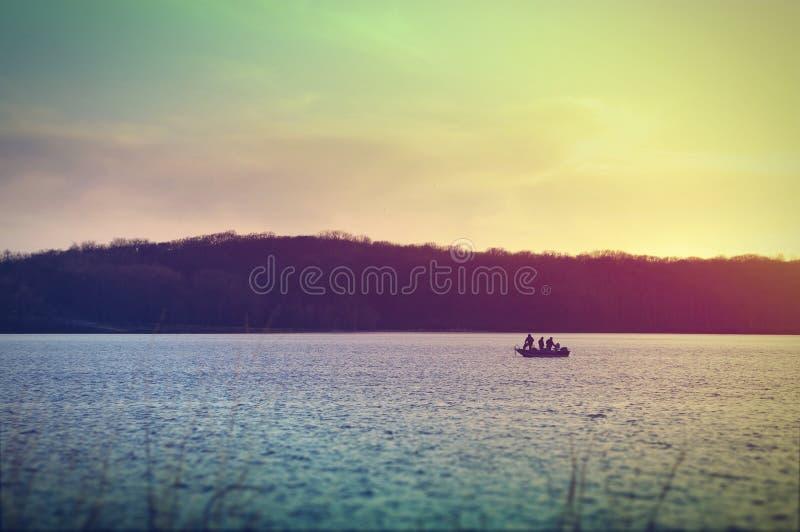 Рыболовы на шлюпке на озере Macbride после захода солнца стоковое фото