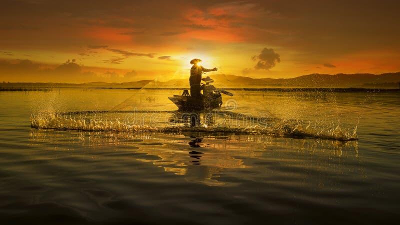 Рыболов азиатских людей на озере в действии удя стоковые изображения rf