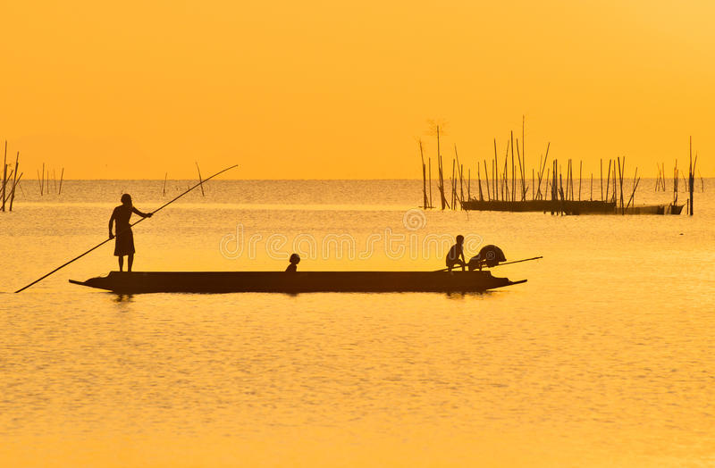 Рыболов бить его шлюпку после удить в заходе солнца на озере Songkhla, Songkhla, Souhtern Таиланда стоковая фотография