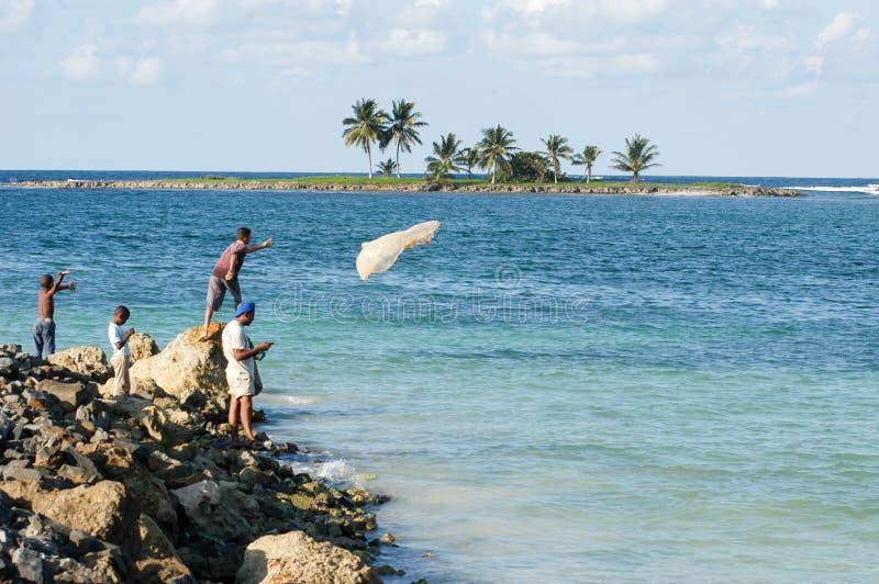 Рыболов бросая рыболовную сеть в море стоковые фото
