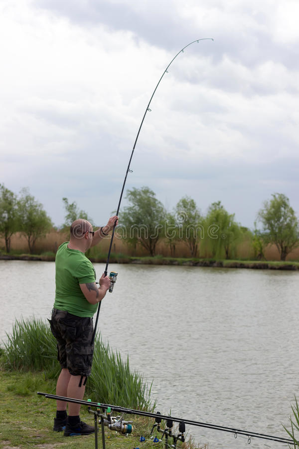 Рыболов в действии, крепежный стержень рыболова в действии стоковое фото