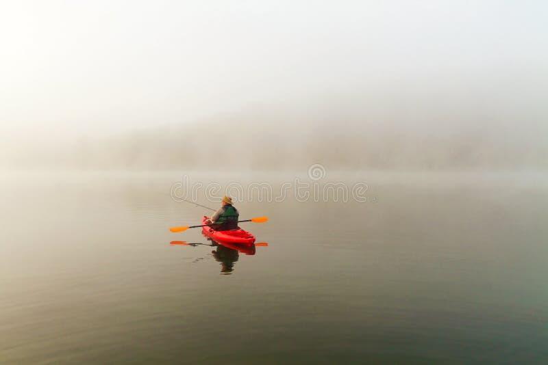 Рыболов в красном каяке стоковое фото