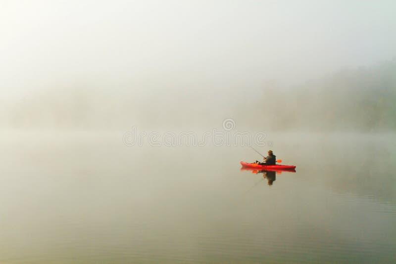 Рыболов в красном каяке стоковая фотография