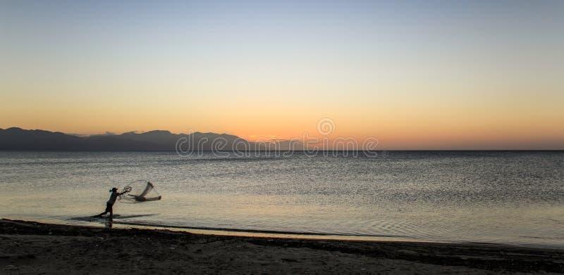 Рыболов в Trujillo, Гондурасе, после захода солнца стоковое фото