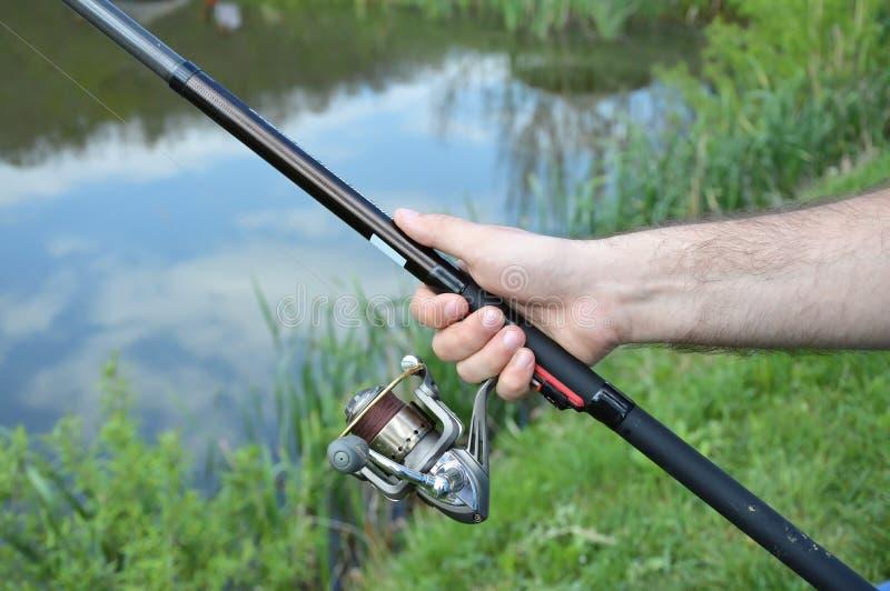 Рыболов держа рыболовную удочку стоковая фотография
