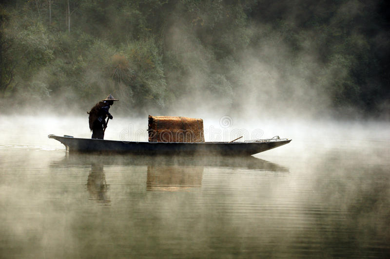 Рыболов и его шлюпка в туманном утре стоковые фото