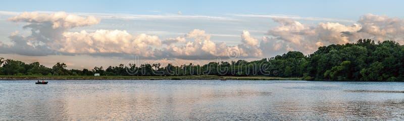 Рыболов на озере на заходе солнца стоковое фото rf