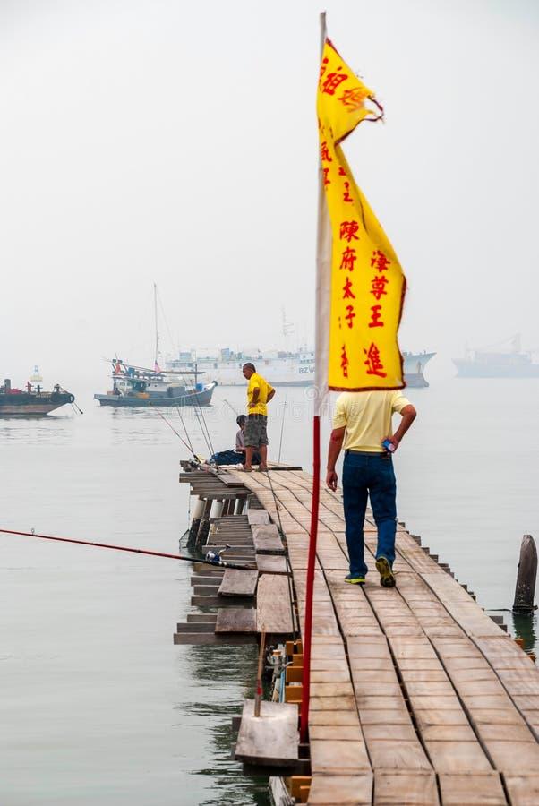 Рыболов на пристани в городке Джордж стоковое фото