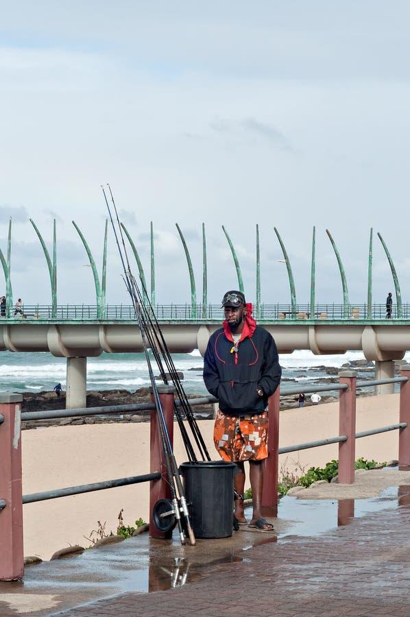 Рыболов на пляже около пристани тысячелетия в Umhlanga трясет стоковое изображение rf