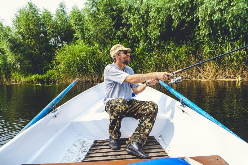 Рыболов при ходы бороды закручивая от шлюпки стоковые фотографии rf