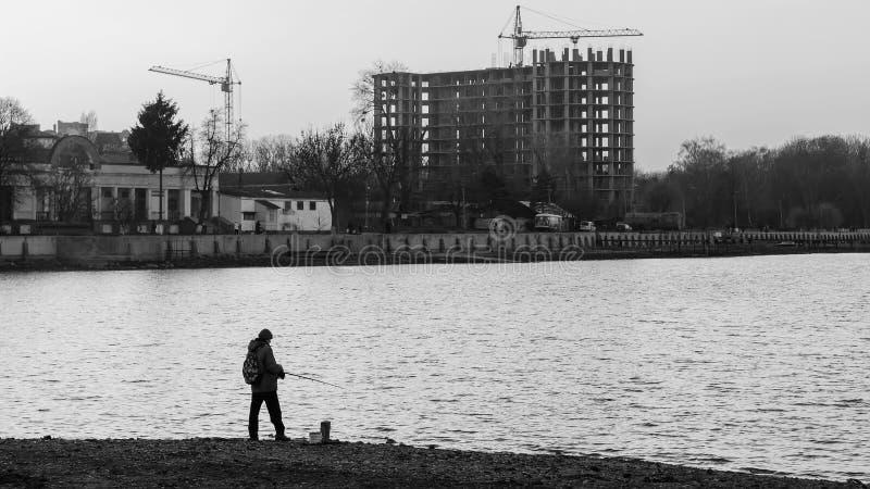 Рыболов стоя на крае берега с рыболовной удочкой около реки в городе, черно-белом стоковые фотографии rf