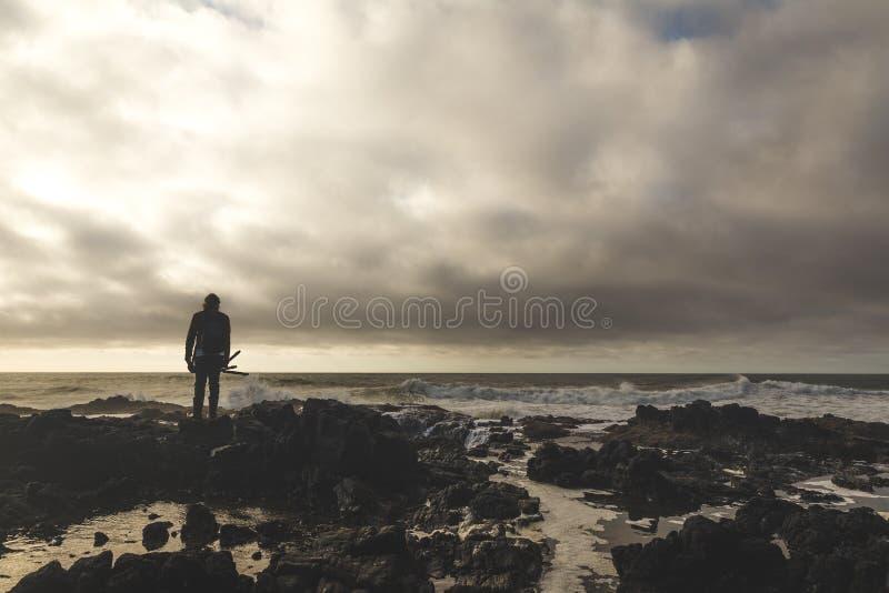 Рыболов стоя на скалистом береге стоковая фотография rf