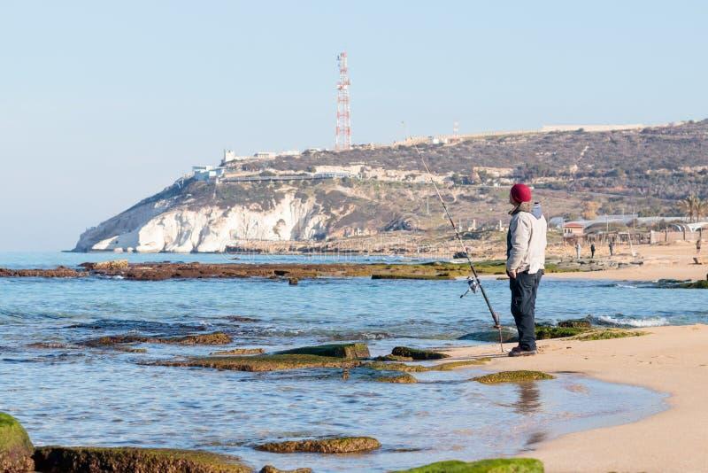 Рыболов улавливает рыбу на закручивать на утро зимы стоковая фотография