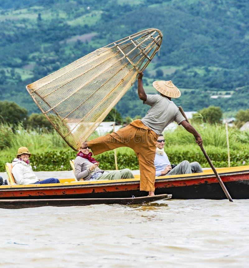 Рыболов Intha представляя для туристов на озере Inle стоковые фото