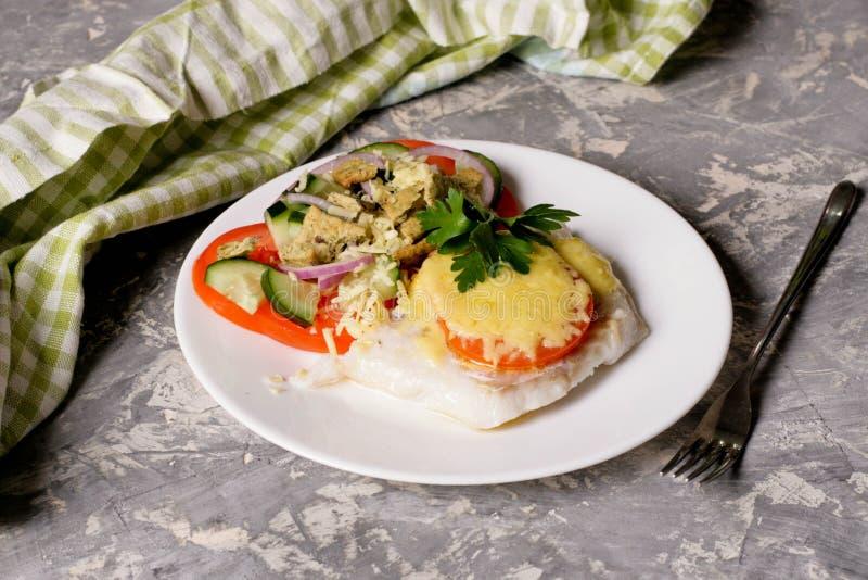 Рыбы испекли с сыром и томатами на белой плите стоковые изображения