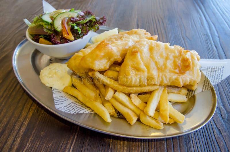 Рыбы и обломоки с салатом стоковая фотография