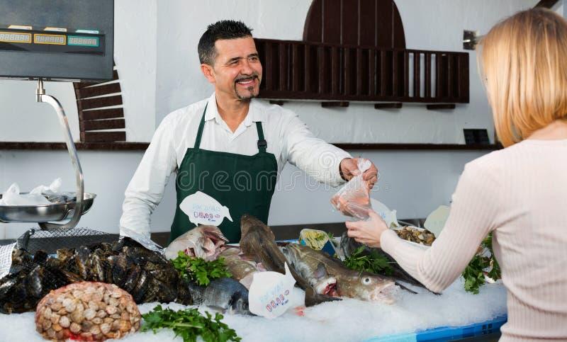 Рыбы работника магазина жизнерадостные продавая свежие и охлаженные морепродукты стоковое фото rf