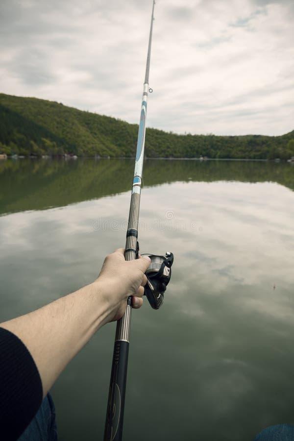Рыбы рыбной ловли от берега с ручкой стоковое фото