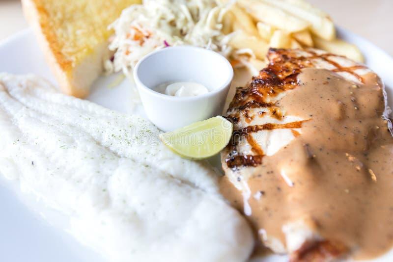 Рыбы тележки и стейк цыпленка, французские фраи, хлеб чеснока и соль стоковые фотографии rf