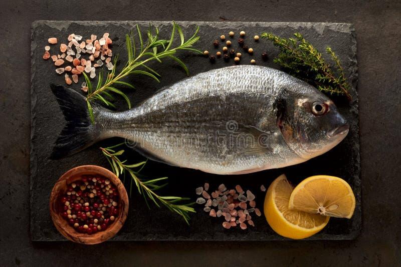 Рыбы Dorado на камне с перцем и солью розмаринового масла лимона в коричневом шаре на деревянной предпосылке стоковое изображение rf