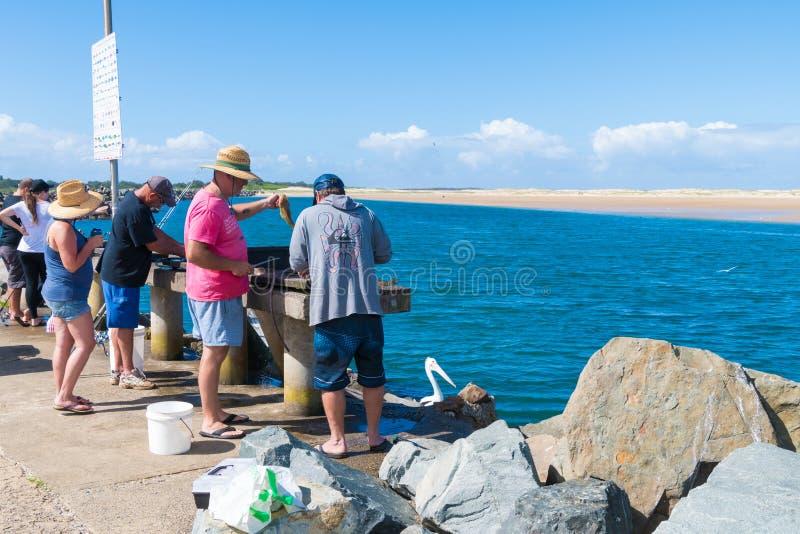 Рыбы Fishermans очищая в небольшом рыбацком поселке головы Crowdy, известном для breakwall используемого как сценарная прогулка и стоковые изображения rf