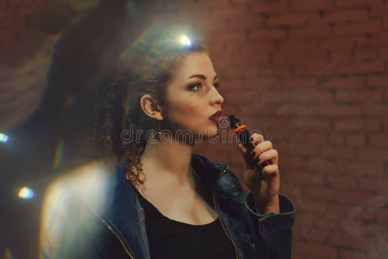 Рыжеволосая девушка курит электронную сигарету стоковая фотография rf