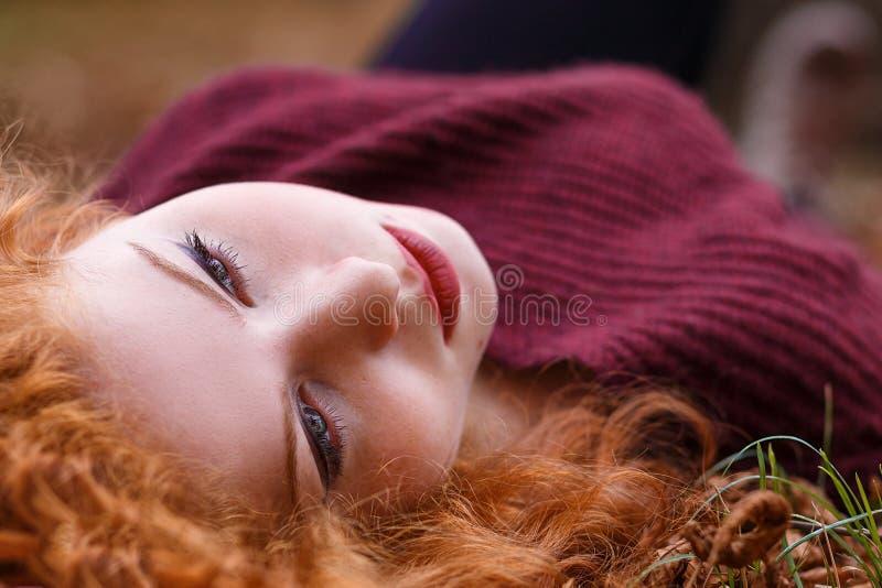 Рыжеволосая девушка лежит в упаденной желтой листве стоковая фотография rf