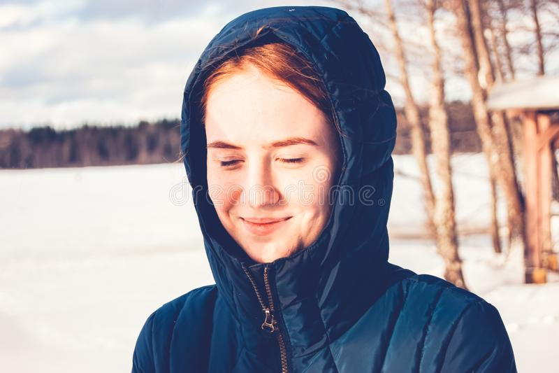 Рыжеволосая девушка радуется в первых лучах солнца весны стоковое изображение