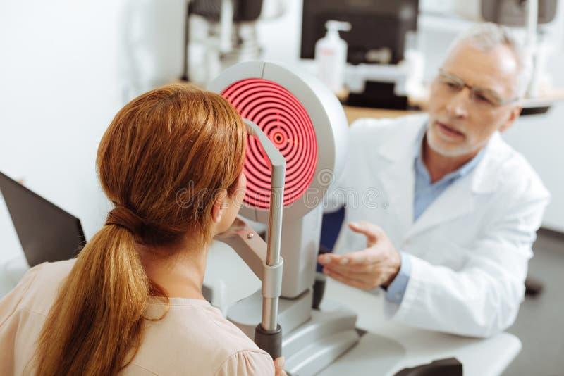 Рыжеволосая женщина сидя перед офтальмологом стоковые изображения rf