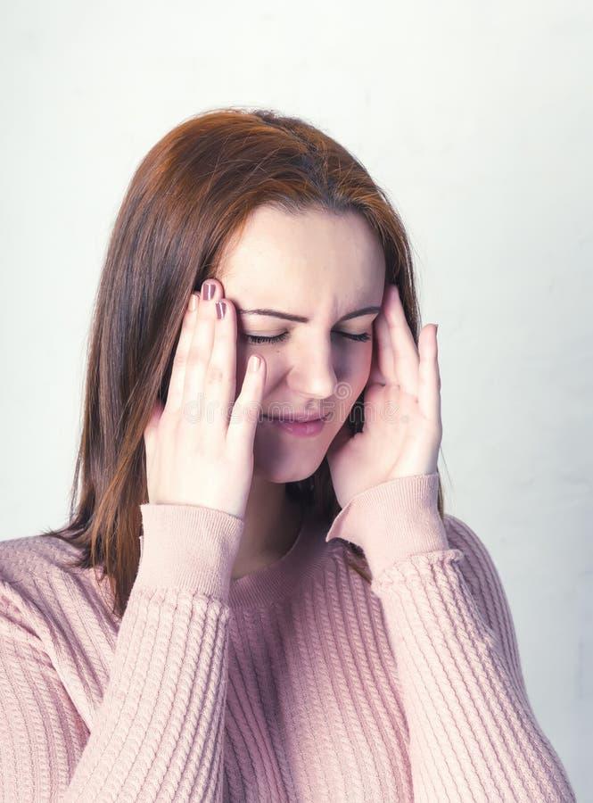 Рыжеволосая маленькая девочка держа ее голову с ее глазами закрыла, головная боль, проблемы, стресс, беспокойство стоковое фото rf