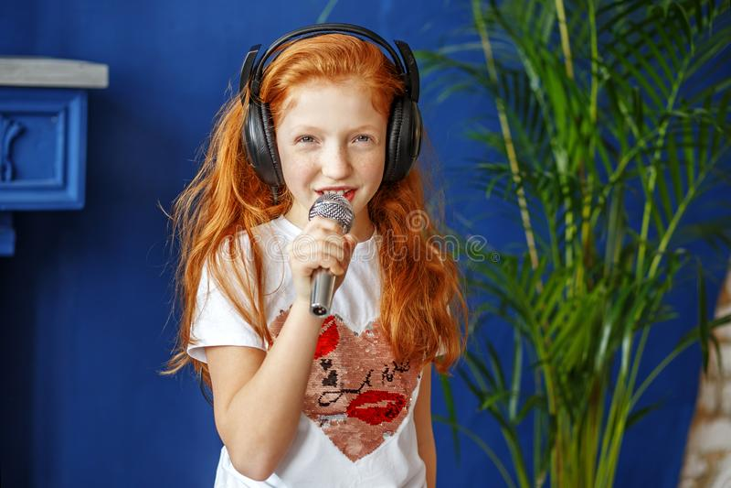 Рыжеволосая маленькая девочка поет песню Концепция детство, стоковое фото rf