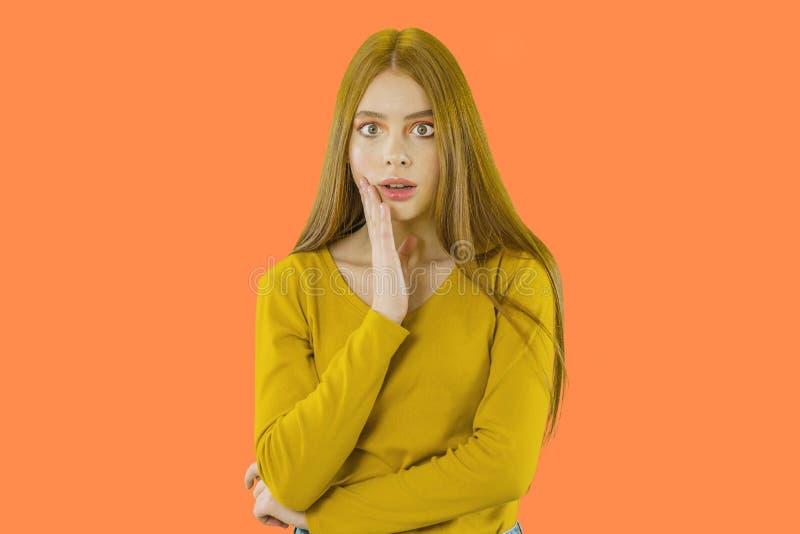 Рыжеволосая маленькая девочка смотрит прочь с вспугнутым выражением лица подпирая вверх одну руку на изолированной предпосылке стоковые фото