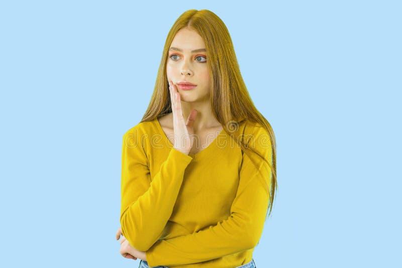 Рыжеволосая маленькая девочка смотрит прочь с задумчивым выражением на ее стороне, подпирая вверх ее сторону с одной рукой на син стоковое фото rf