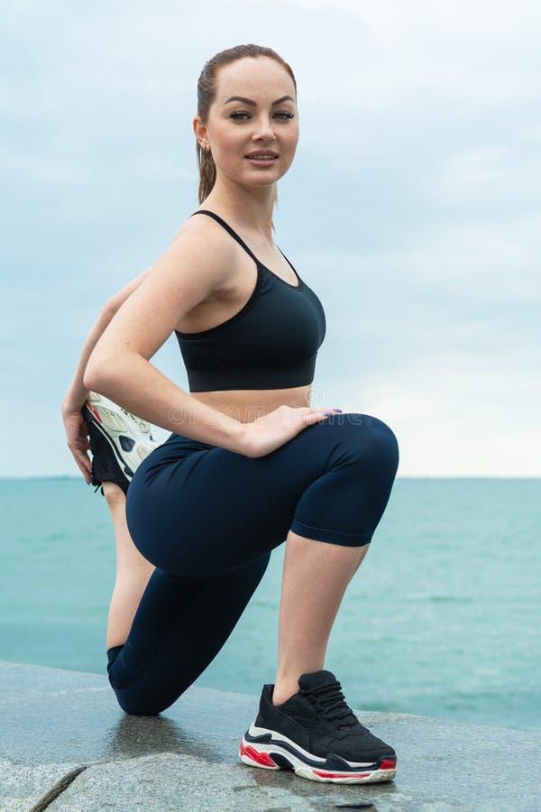 Рыжеволосая, молодая, атлетическая, красивая девушка принималась за гимнастику, бег на открытом воздухе Выполняет тренировки спор стоковые изображения