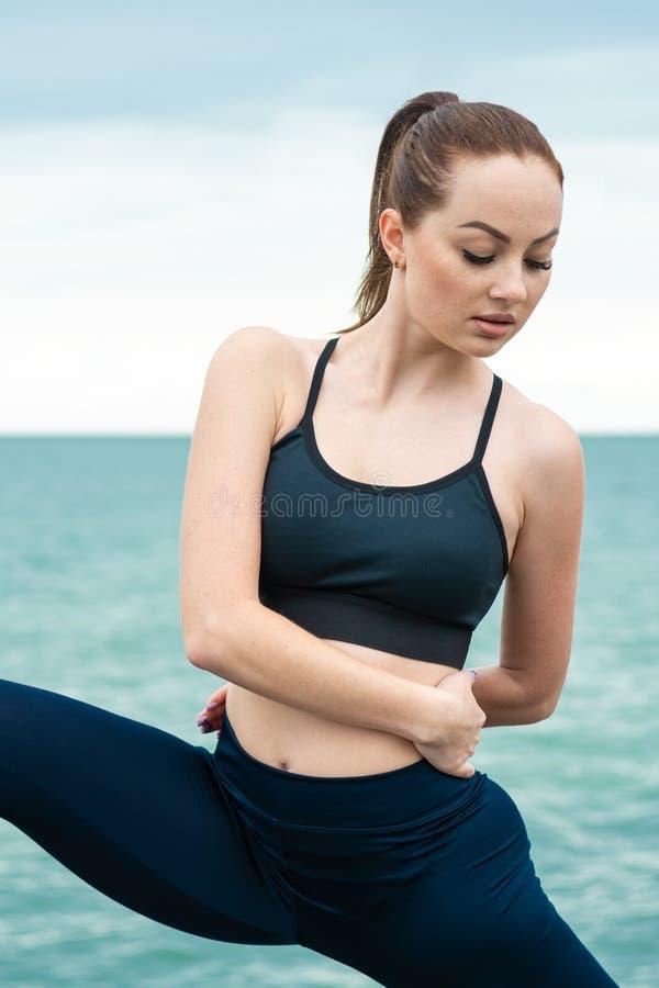 Рыжеволосая, молодая, атлетическая, красивая девушка принималась за гимнастику, бег на открытом воздухе Выполняет тренировки спор стоковая фотография