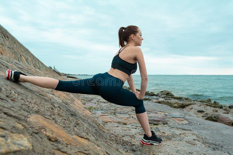 Рыжеволосая, молодая, атлетическая, красивая девушка принималась за гимнастику, бег на открытом воздухе Выполняет тренировки спор стоковые фото