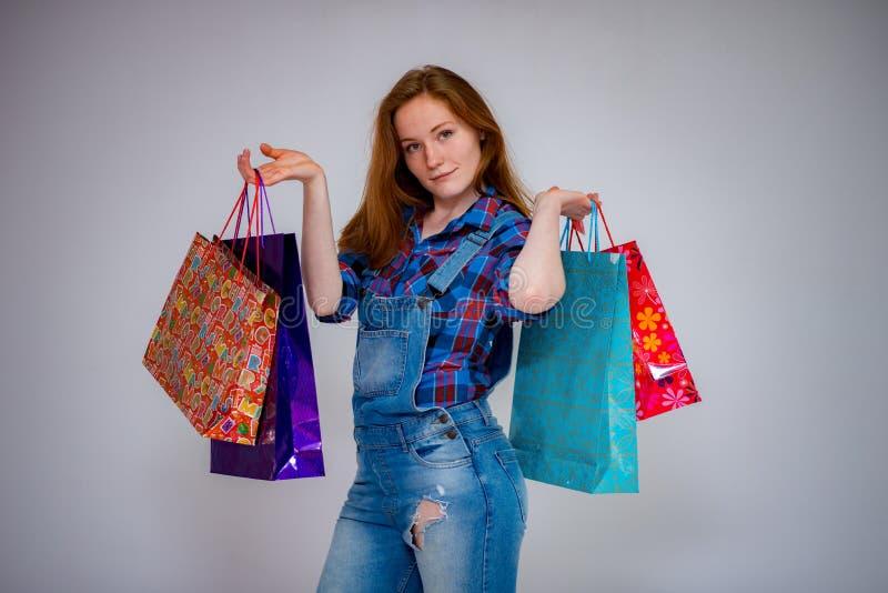 рыжеволосые красивые хозяйственные сумки молодой женщины стоковое изображение