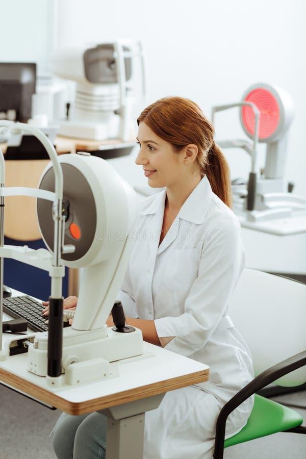 Рыжеволосый глазной врач используя современные технологии пока работающ стоковые изображения rf