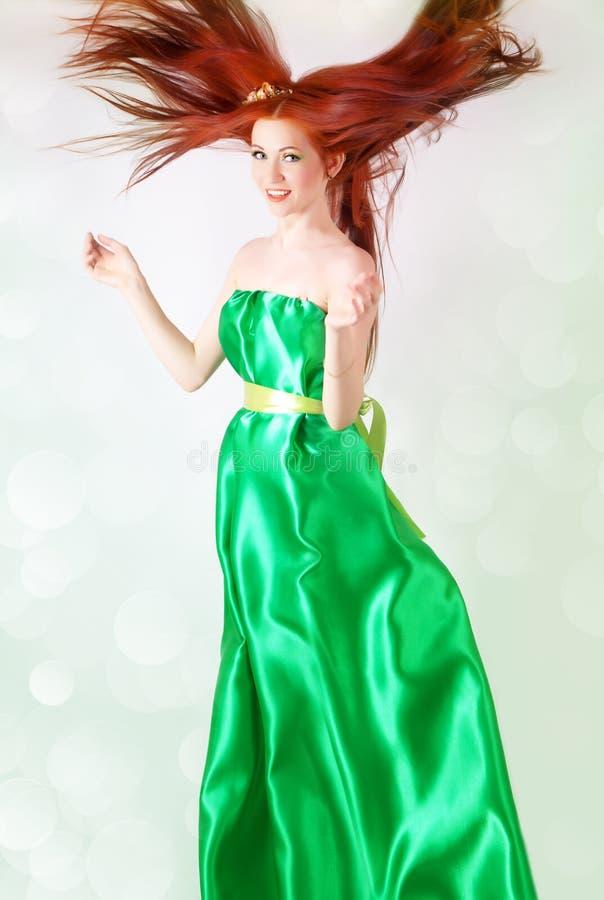 Рыжеволосая девушка в зеленом платье с пропуская волосами стоковая фотография rf
