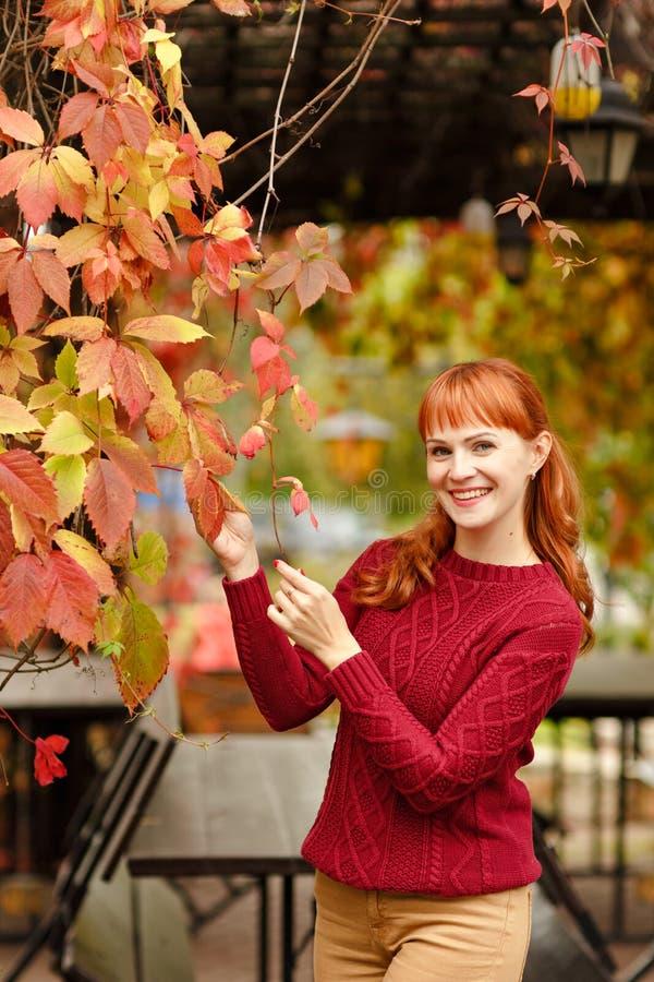 Рыжеволосая девушка в усмехаться свитера счастливый на предпосылке осени стоковые изображения rf