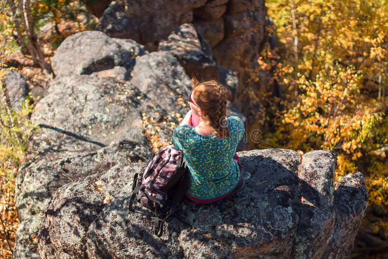 Рыжеволосая девушка сидя на утесе с рюкзаком на backgro стоковое изображение