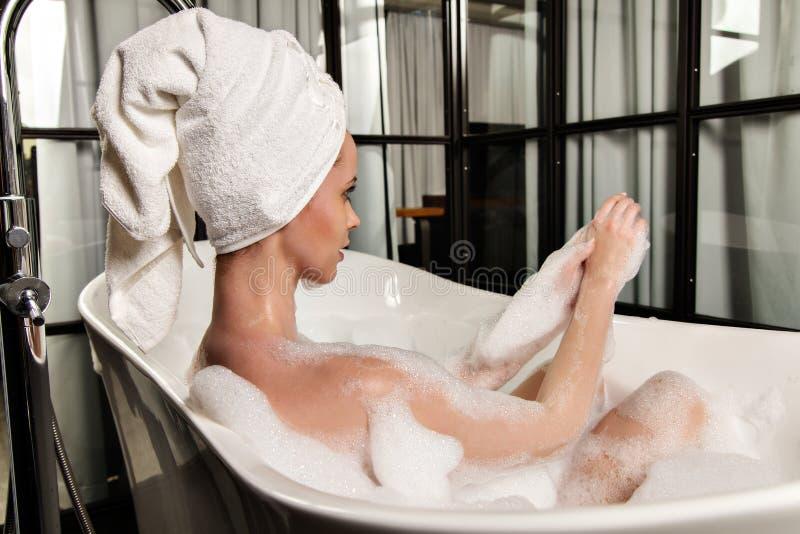 Рыжеволосая красивая молодая женщина с полотенцем на ее голове после ванны стоковая фотография rf