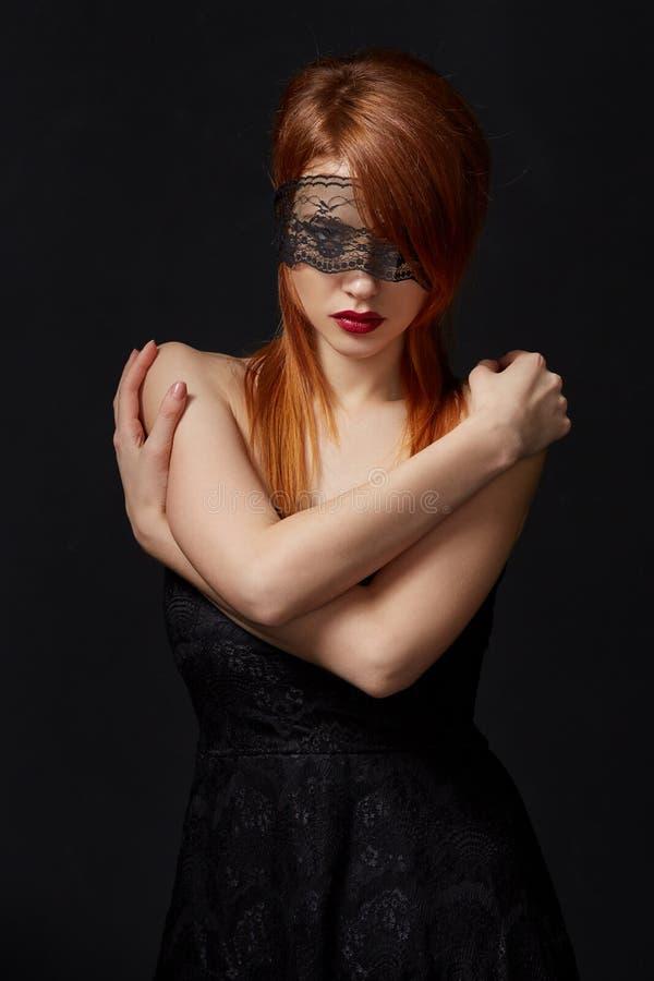 Рыжеволосая красота с маской шнурка на глазах стоковая фотография rf