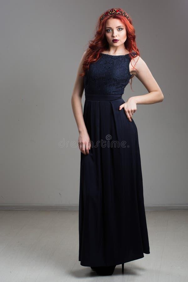 Рыжеволосый модельный представлять в платье вечера и в diadem стоковые изображения